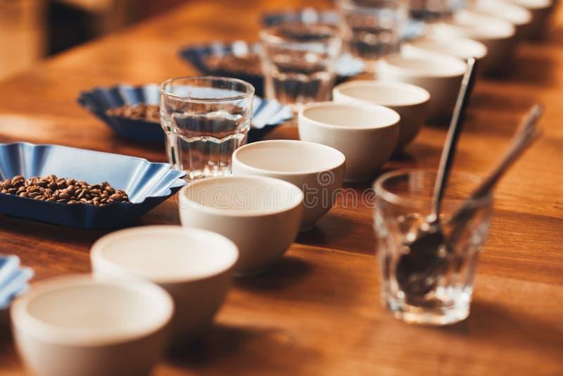 Kaffeetassen und Bohnen auf tischfertigem für ein Probieren stockfoto
