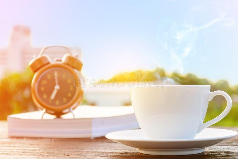 Kaffeetasseuhr und Nachrichtenpapier auf altem Holztisch stockfoto
