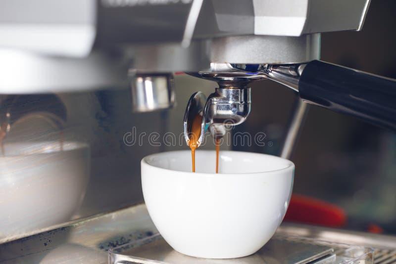 Kaffeextraktion som häller in i en kopp från yrkesmässig kaffemor arkivfoton