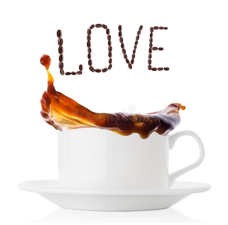 Kaffefärgstänk i den vita koppen med tefatet och inskriften älskar kaffebönor royaltyfria foton