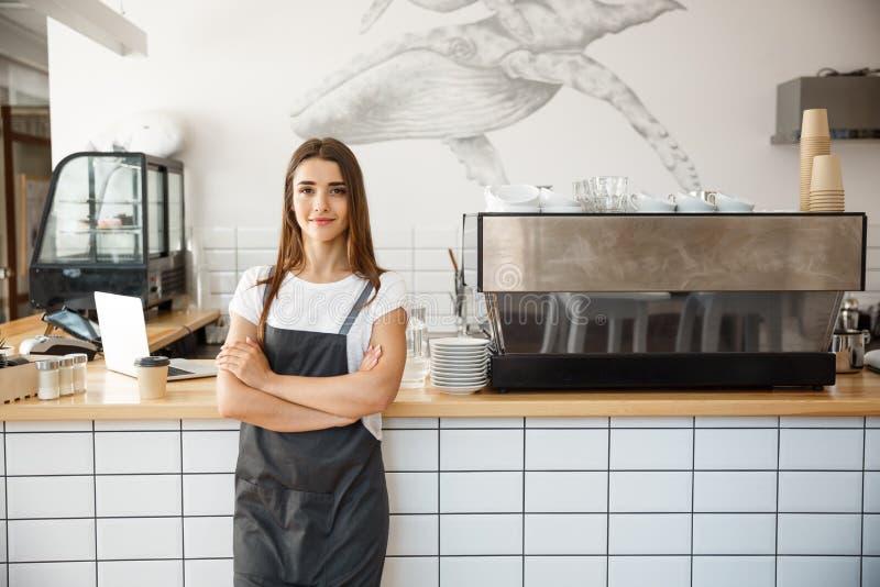 Kaffeföretagsägare Concept - stående av den lyckliga attraktiva unga härliga caucasian baristaen i förklädet som ler på royaltyfria foton