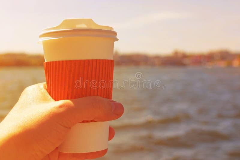 Kaffekopp i hand mot bakgrunden av sjön på solnedgången royaltyfri bild