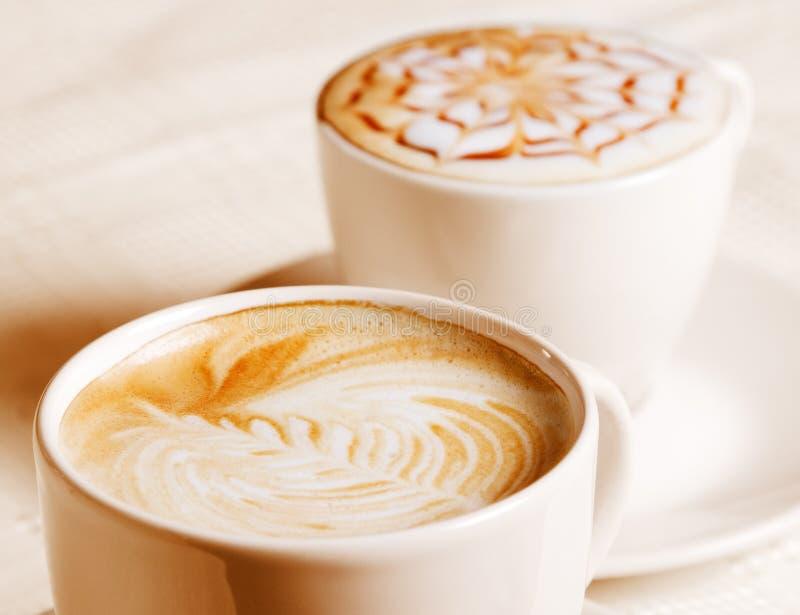 Kaffekopp med den konstnärliga kräm- garneringen arkivbilder