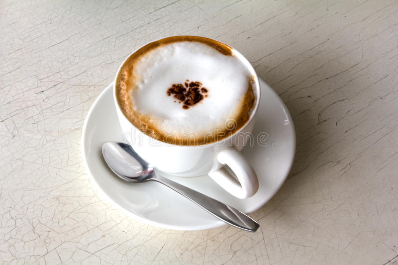 Kaffekopp med den konstnärliga kräm- garneringen fotografering för bildbyråer