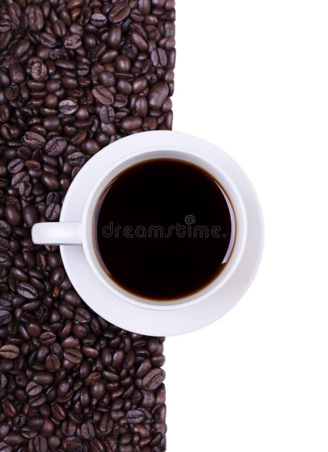 Kaffekopp med espressokaffebönor arkivfoton