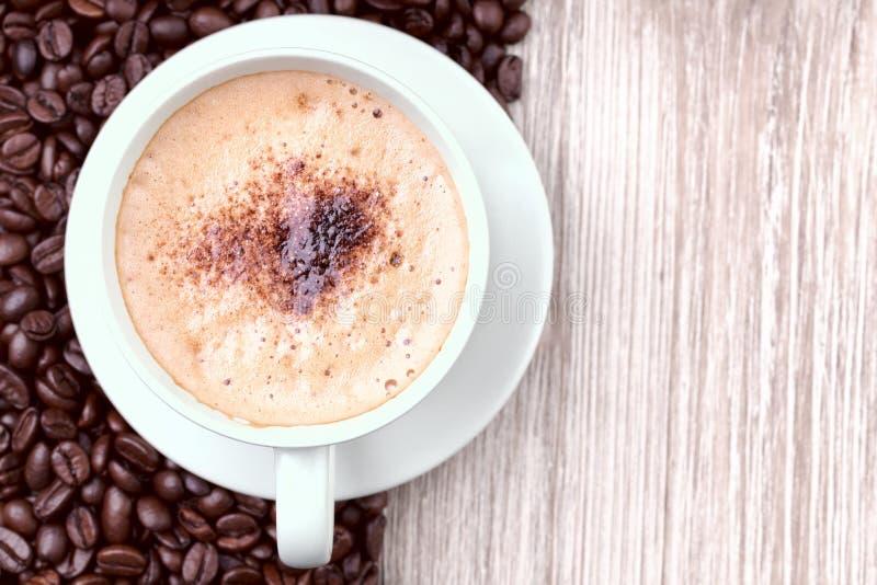 Kaffekopp med grillade kaffebönor arkivbilder