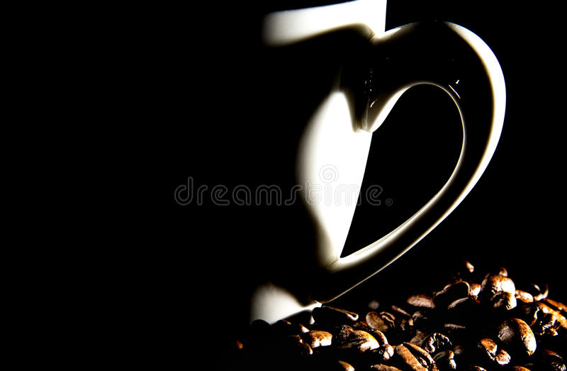 Kaffekopp med hjärtaskugga- och kaffebönor royaltyfria foton