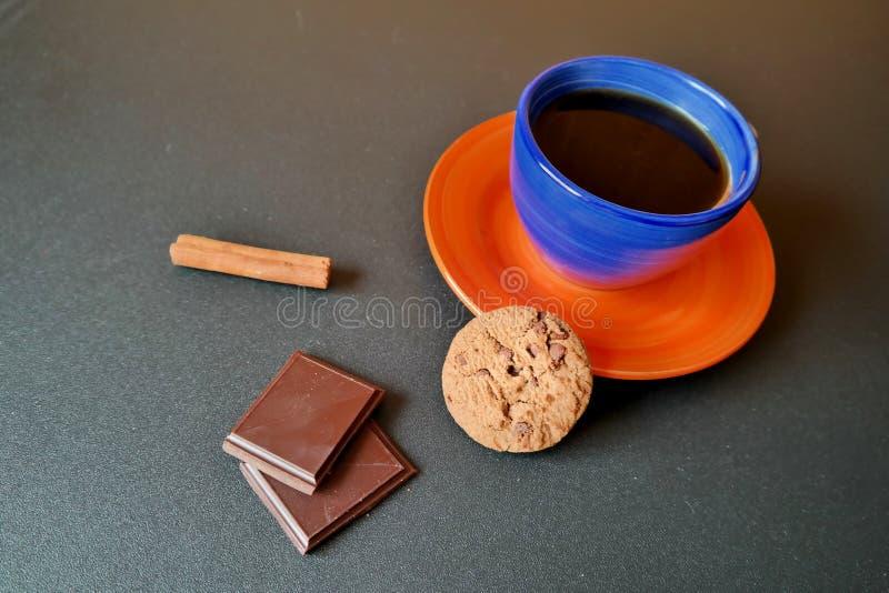 Kaffekopp med kakor, choklad och kanelbrun rulle arkivfoto