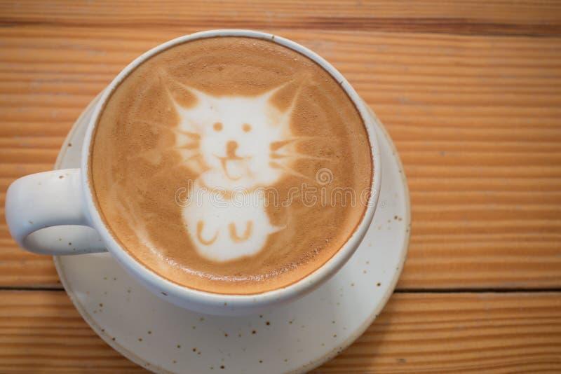 Kaffekopp med konstnärlig kräm- kattframsidagarnering royaltyfri foto