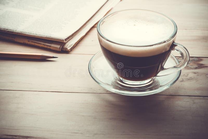 Kaffekopp med newpaper på den wood tabellen i morgon royaltyfria foton
