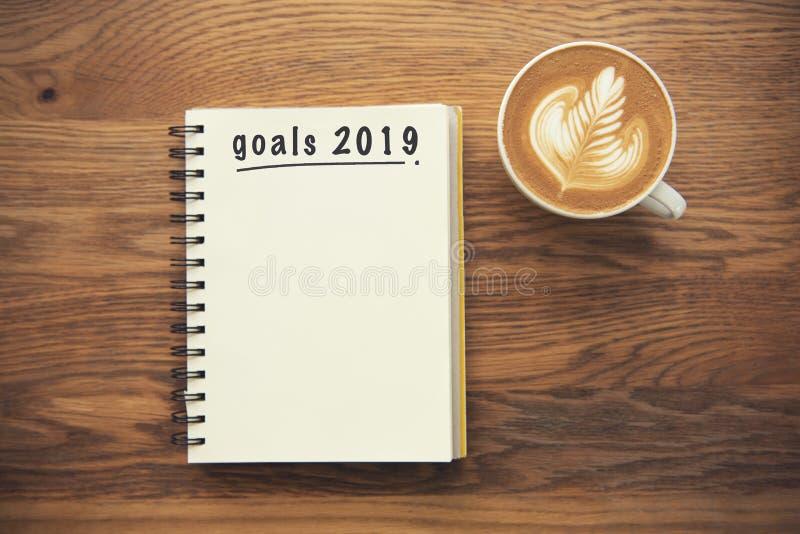 Kaffekopp och anteckningsbok med mål 2019 på det lantliga skrivbordet arkivfoton