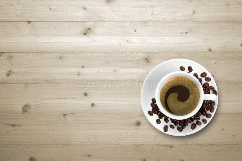 Kaffekopp och bönor på trätabellen arkivbilder