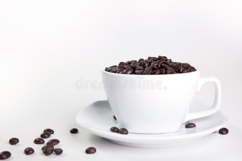 Kaffekopp och b?nor p? en vit bakgrund arkivbild