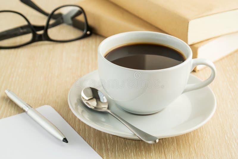Kaffekopp och bok på tabellen royaltyfri fotografi