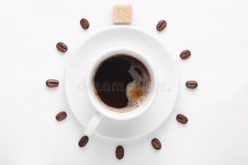 Kaffekopp och kaffebönor med kuben för rottingsocker mot vit bakgrund som bildar klockavisartavlan som beskådas från överkant arkivbilder