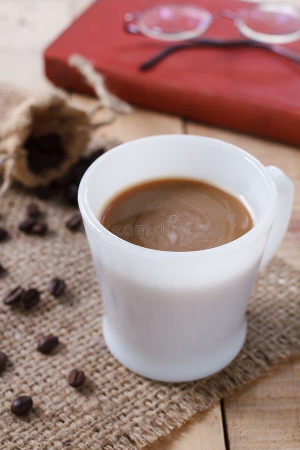 Kaffekopp och kaffebönor på matt säckväv, valfokus royaltyfri fotografi