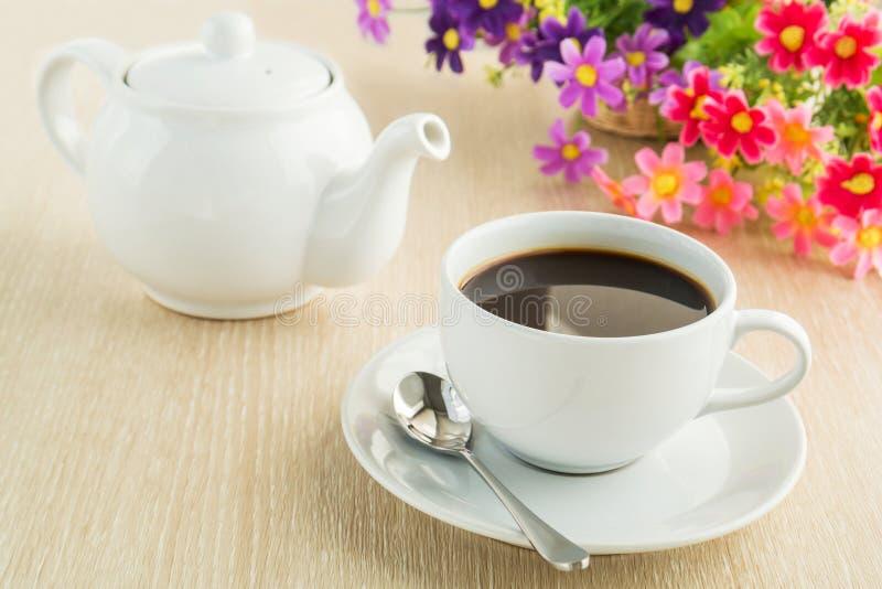 Kaffekopp och kruka på tabellen arkivfoton