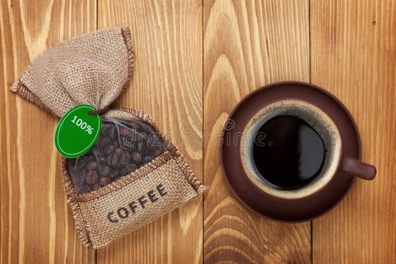 Kaffekopp och liten påse med bönor fotografering för bildbyråer
