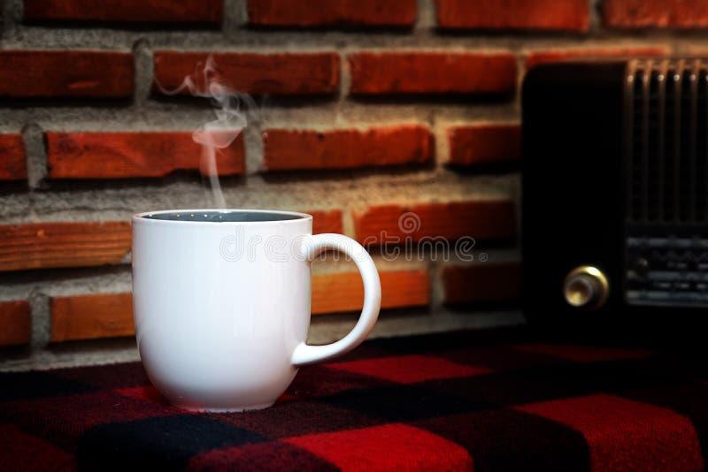 Kaffekopp och Reto radio på tabellen arkivfoto