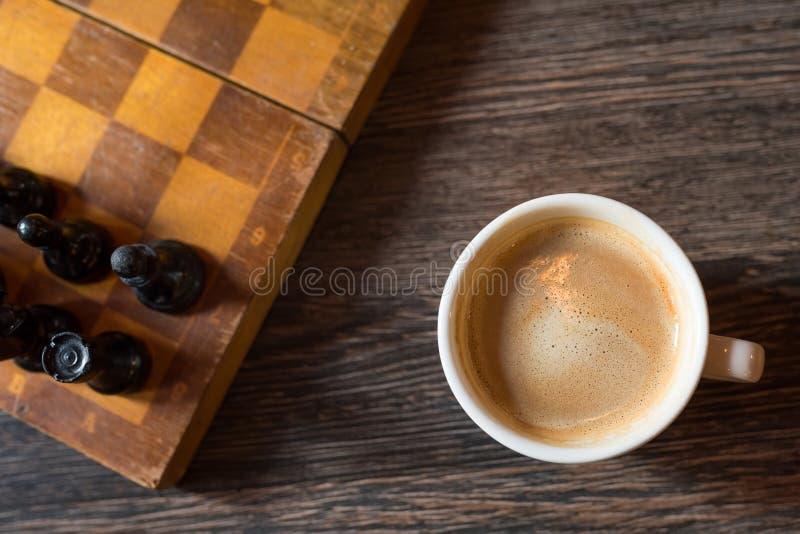 Kaffekopp på bakgrunden av en schackbräde Top beskådar arkivbilder