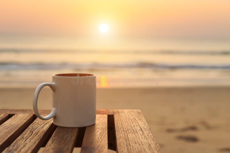 kaffekopp på den wood tabellen på solnedgången eller soluppgångstranden fotografering för bildbyråer
