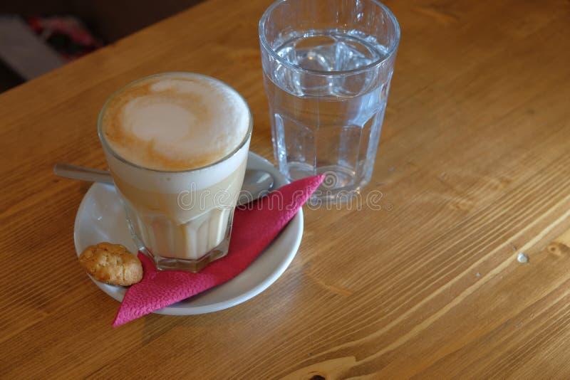 Kaffekopp på tabellen på sourcer med sked- och kakavinkelsikt royaltyfri bild