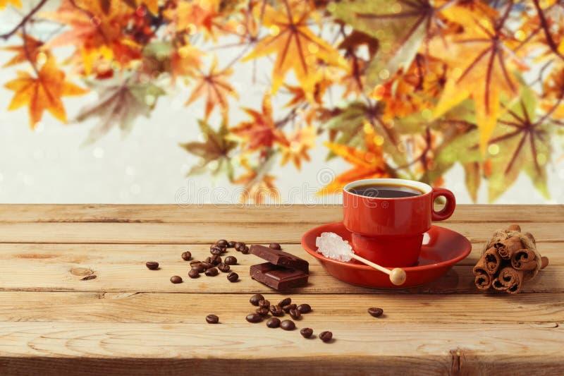 Kaffekopp på trätabellen över bakgrund för höstsidor fotografering för bildbyråer