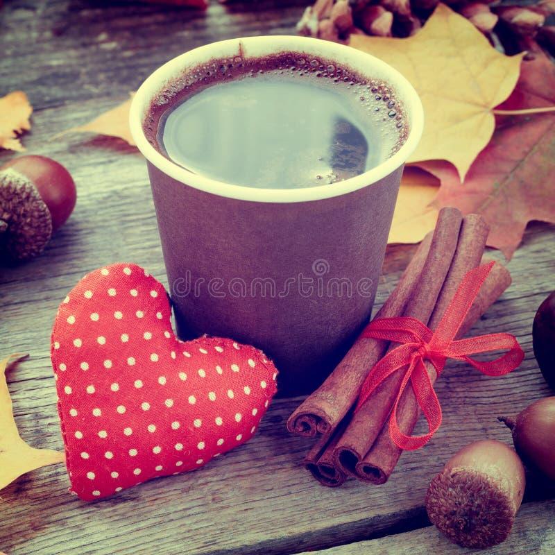 Kaffekopp, röd hjärta och höststilleben på tabellen royaltyfri foto