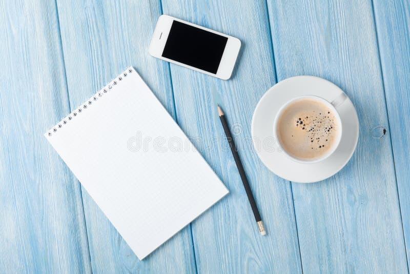 Kaffekopp, smartphone och mellanrumsnotepad på trätabellbac royaltyfria bilder