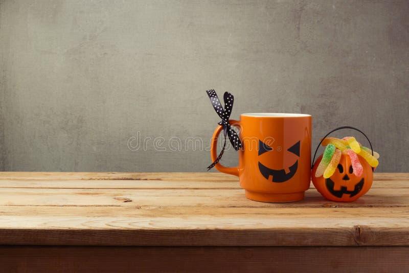 Kaffekopp som pumpa och godisen för stålarnolla-lykta för trick eller fest på trätabellen för den grymma säger miniatyrreaperen h arkivbilder