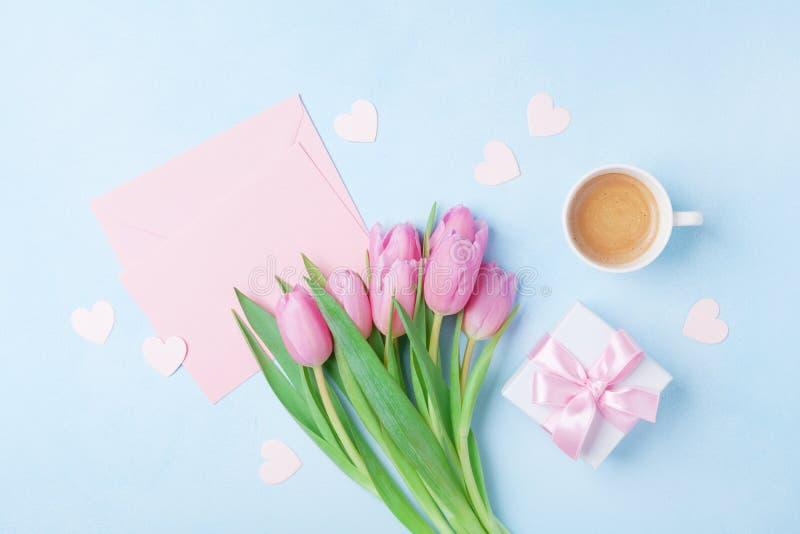 Kaffekopp, vårtulpanblommor, gåvaask och rosa pappers- kort på blå pastellfärgad bästa sikt för tabell Hälsning för kvinnas eller royaltyfria bilder