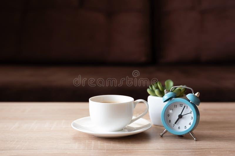 Kaffekoppar, blomkruka och klocka på träbord mot sockor med avskärmat kudde Framifrån God morgon-konceptet Mock-up royaltyfria foton