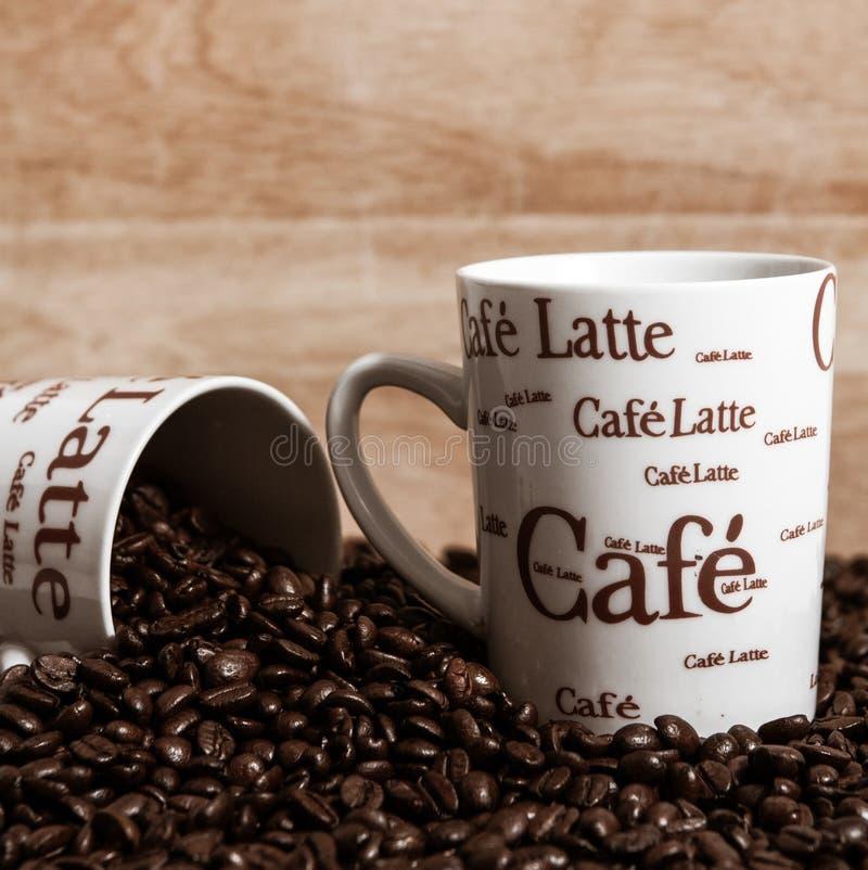 Kaffekoppar och kaffebönor arkivbild