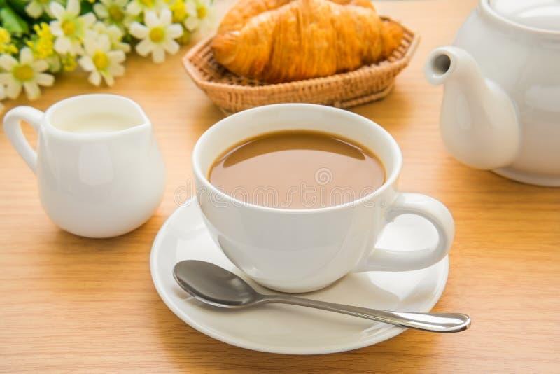 Kaffekoppen, mjölkar och gifflet på trätabellen royaltyfri bild