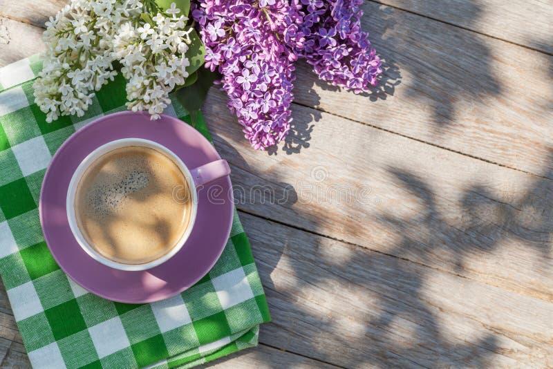 Kaffekoppen och den färgrika lilan blommar på den trädgårds- tabellen royaltyfri foto