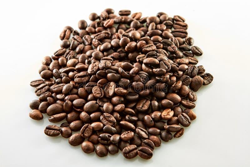 Kaffekorn glider isolerat på vit arkivbild