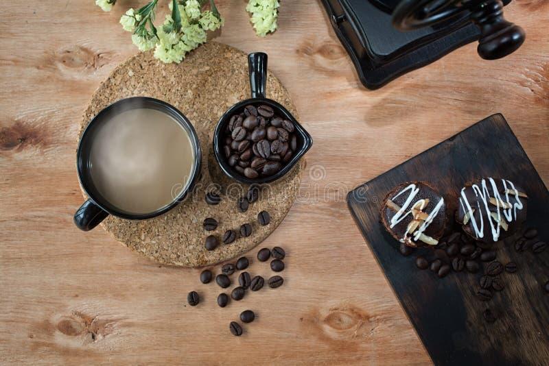 Kaffekvarn-, kaffeböna, kaffe och sötsaker Kaffekopp och s?tsaker p? tr?tabellen royaltyfria foton