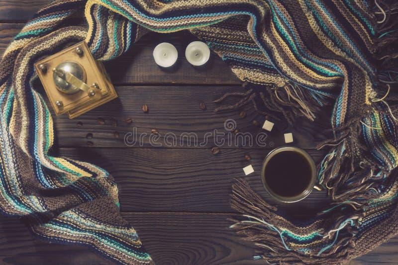 Kaffekvarn, kopp, stearinljus och varm halsduk på en trätabell Top beskådar royaltyfri bild