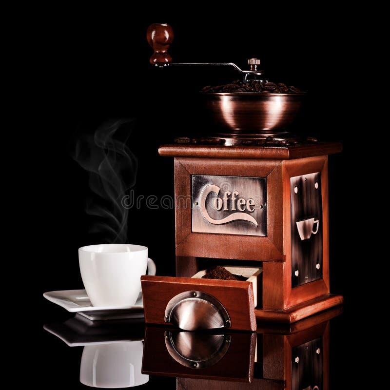 Kaffekvarn med espressokoppen och svartbakgrund royaltyfri foto