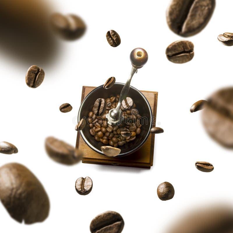 Kaffekvarn- och kaffebönor i flykten på vit bakgrund arkivbild