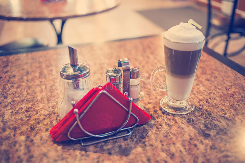 KaffeLatte i ett exponeringsglas på den preshious bubingo-wooodtabellen, colorized tappningsignaler, grund DOF, selektiv fokus royaltyfri fotografi