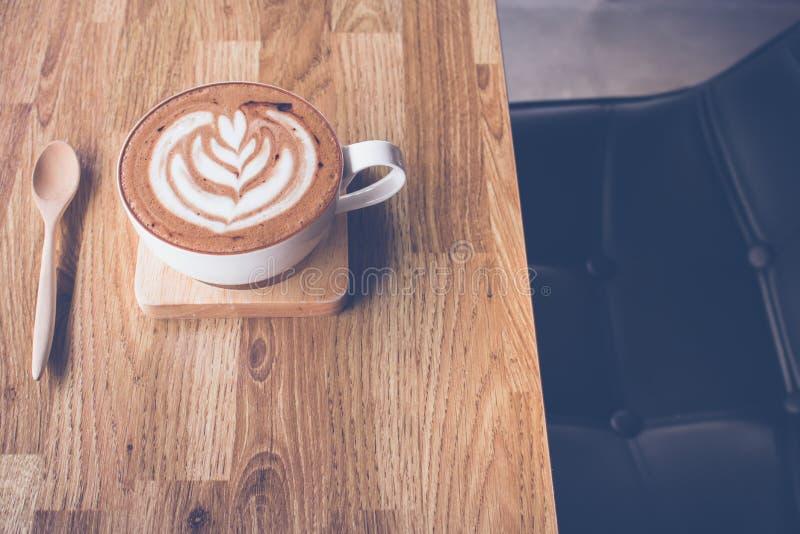 Kaffelattekonst på trätabellen med läderplatsen i kaffesho royaltyfria foton