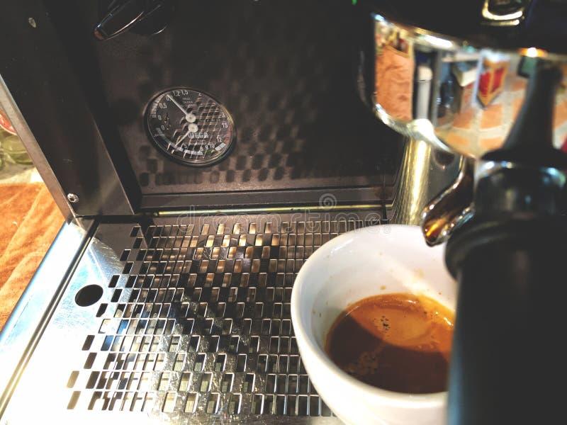Kaffemaskin, espressoskottdroppe på den vita koppen royaltyfri fotografi
