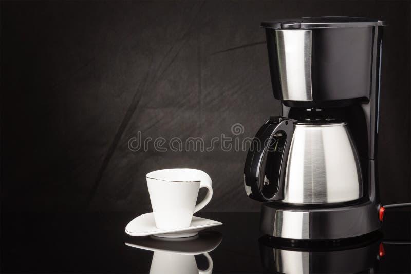 Kaffemaskin med krukan och koppen på den svarta spegelbakgrunden royaltyfri fotografi