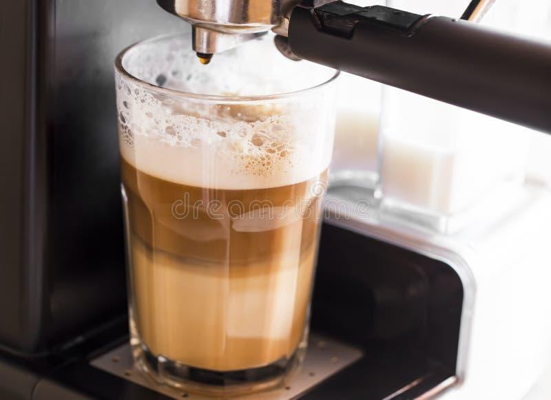 Kaffemaskin som gör lattekaffe i ett genomskinligt exponeringsglas med M royaltyfri fotografi