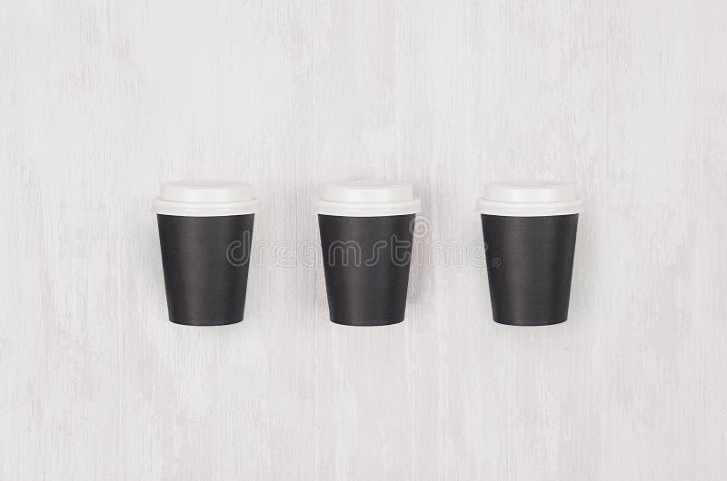Kaffemodellen - ställ in av tre lilla tomma svarta papperskoppar med vita lock på det vita träbrädet, bästa sikt fotografering för bildbyråer