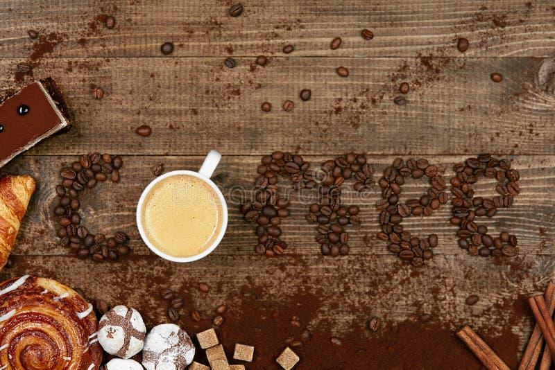 Kaffeord och bönor med koppen kaffe arkivbilder