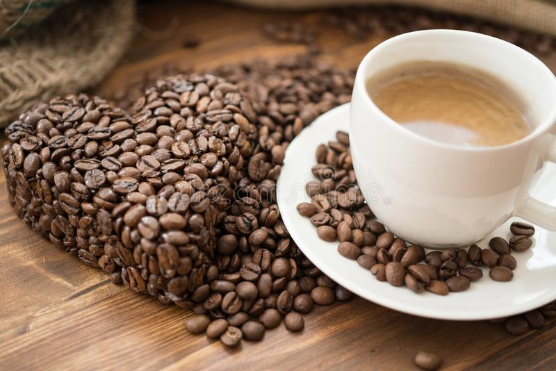 Kaffepåse och hjärta från kaffebönor på tabellen arkivfoton