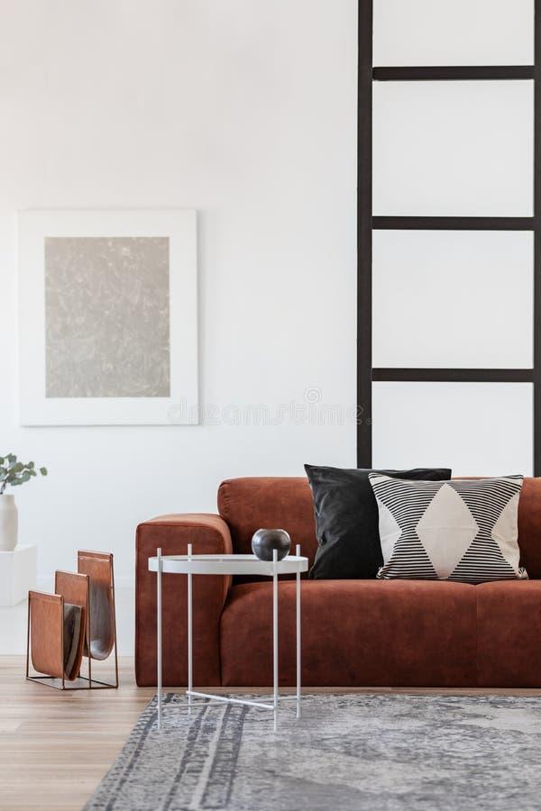 Kaffetabell för vit metall bredvid den bekväma soffan med kuddar arkivbilder