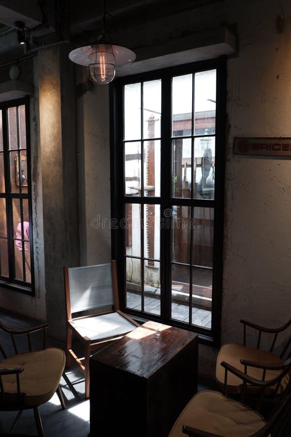 Kaffetabell och stolar nära fönster med vindstil arkivfoto